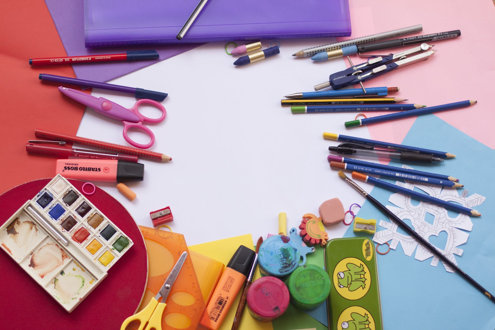 Colorful school supplies scattered on a flat surface with colorful papers on it